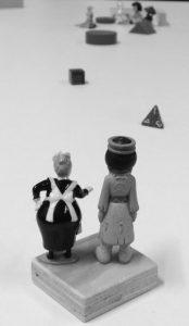 Zwei sehr kleine Figuren stehen mit dem Rücken zum Betrachter und blicken voraus auf kleine Hindernisse.